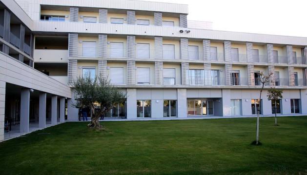 Foto de una de las fachadas del edificio, que asoma al patio interior ajardinado.