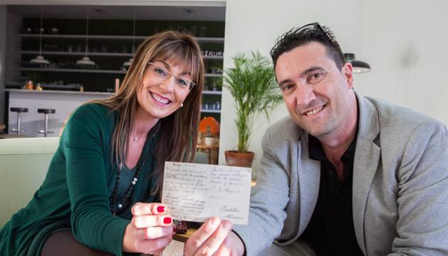 Isuka Navarro -hija de Jesús Navarro Cornago- y Carlos Bueno muestran la postal  que éste le entregó ayer en el Aire de Bardenas.