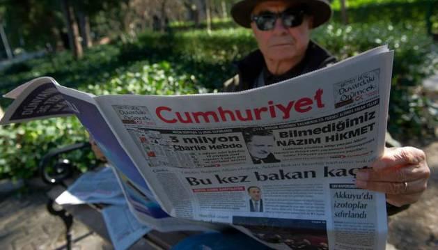 Un hombre sostiene un ejemplar del diario Cumhuriyet de Turquía.