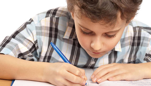 Un niño hace los debes en su casa.