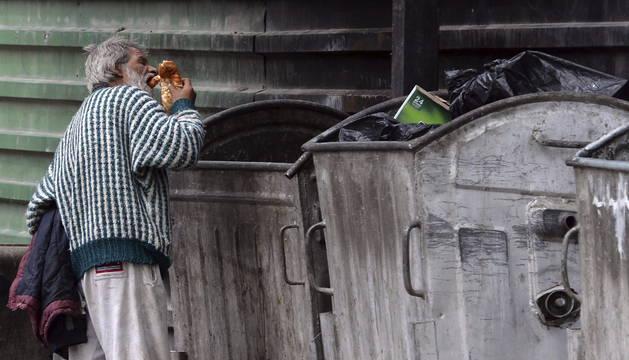 Un indigente coge comida de un contenedor en la calle.