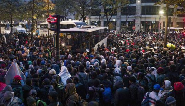 Centenares de inmigrantes esperan para subir a un autobús durante el desalojo de un campamento en el distrito 19 de París.
