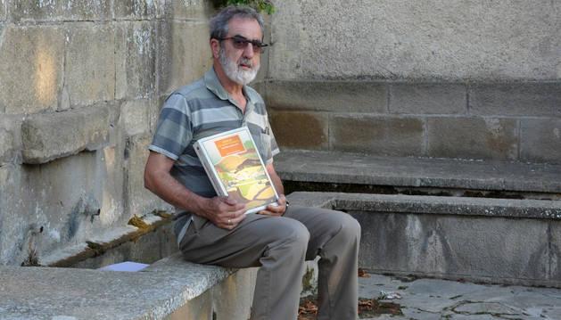 Foto de Juan José Ojer muestra en Unzué el libro que ha publicado.
