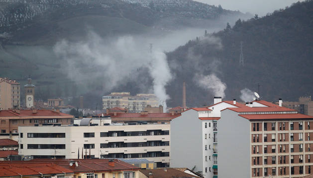 Vista general de los tejados de unos edificios de Pamplona con chimeneas encendidas en pleno invierno.