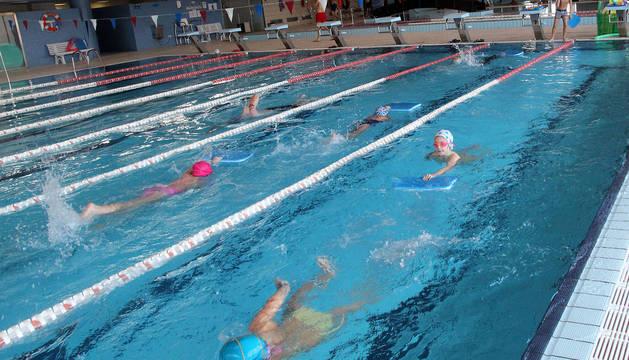 Niños del colegio Compañía de María nada en la piscina cubierta municipal de Tudela durante su clase de Educación Física