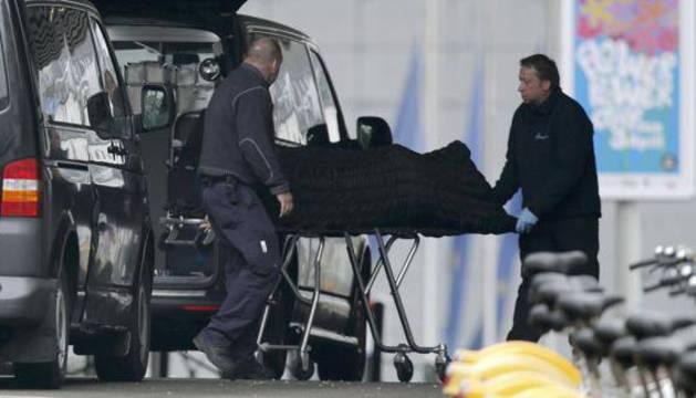 Dos personas retiran uno de los cádaveres del atentado de Bruselas.