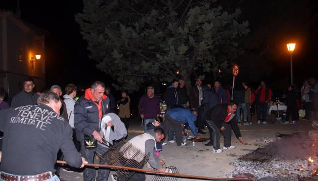 Varios vecinos asan distintos alimentos sobre las brasas de la hoguera con motivo de la fiesta de San Martín.