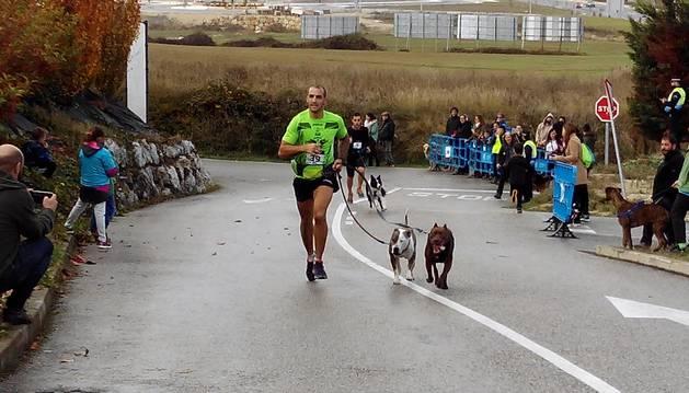 Una participante corre junto a su perro en el I Canicross Solidario.
