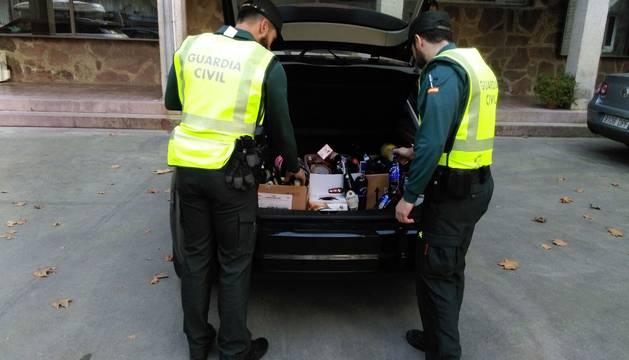 Dos agentes junto a las botellas de alcohol incautadas a los detenidos.