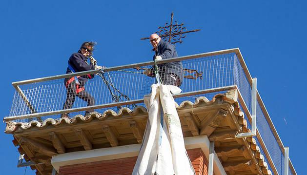 Dos integrantes de Gurelur retiran el nido de cigüeña instalado en la guardería del Niño Jesús de Corella.