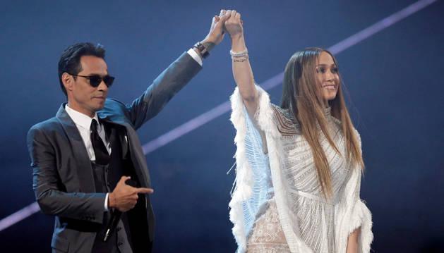 Los cantantes Jennifer Lopez (d) y Marc Anthony saludan a los asistentes después de darse un beso durante los premios Grammy Latino
