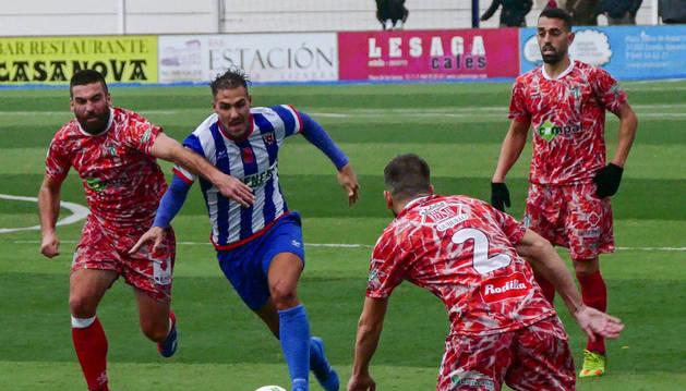 Yoel Sola, mediocentro del Izarra que se retiró ayer lesionado, conduce el balón rodeado por tres rivales del Guijuelo ayer.