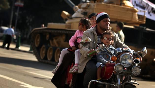 Una familia con dos niños pasa junto a un tanque en El Cairo.