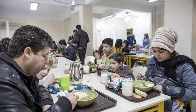 Varias personas disfrutan de un plato caliente en un comedor social.