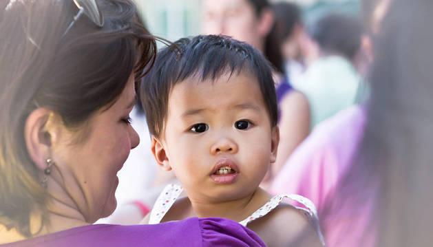 Imagen de una mujer mira a una niña de otra raza.