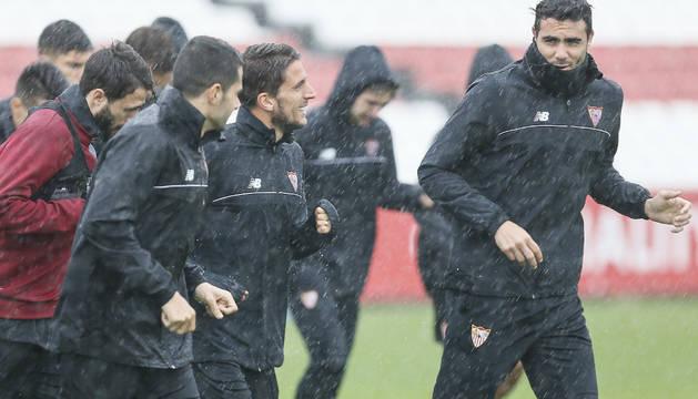 Los jugadores del Sevilla han preparado el partido bajo un fuerte aguacero.