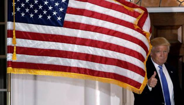Donald Trump posa tras una bandera de Estados Unidos.