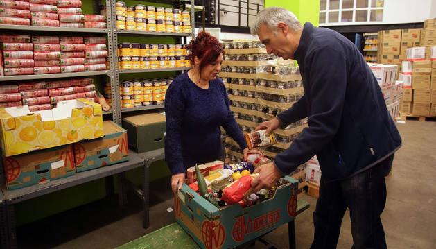 María, de 56 años, recibe una caja de comida del voluntario del banco de Alimentos de Berriozar Javier  Labiano.