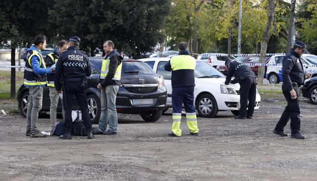 Agentes de la policía, junto al vehículo donde la mujer murió degollada presuntamente por su novio.