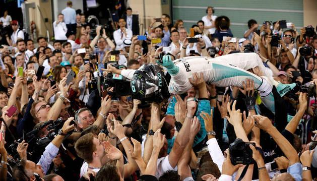Imagen del piloto de Fórmula Uno Mercedes Nico Rosberg de Alemania es llevado por los aficionados después de ganar el campeonato mundial de Fórmula Uno.