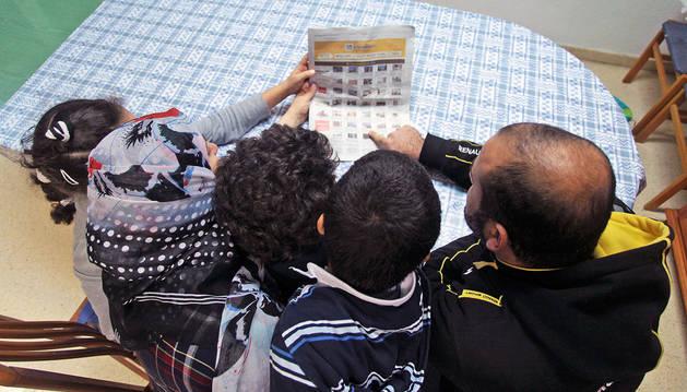 Una familia palestina mira los anuncios clasificados de Diario de Navarra, en busca de un piso.