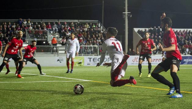 El centrocampista argentino del Sevilla FC Joaquín Correa (3d) cae tras la entrada del jugador del Formentera, durante el partido de ida de dieciseisavos de final de la Copa del Rey que se juega hoy en el estadio municipal de Sant Francesc, en Formentera.