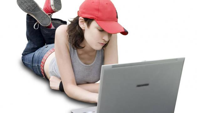 Imagen de una adolescente frente a un ordenador portatil.