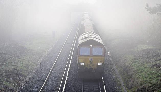 Un tren internacional circula en mitad de la niebla.