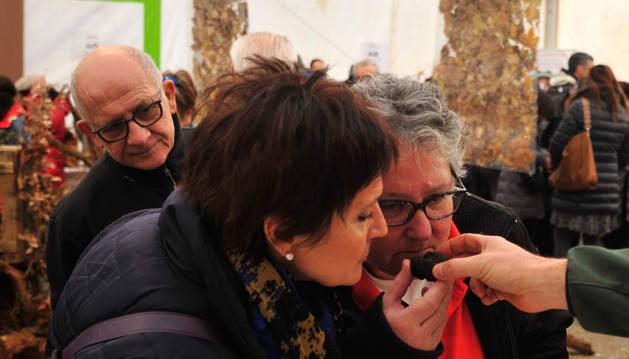Dos mujeres aspiran el aroma de una trufa este domingo en la feria de Orísoain.