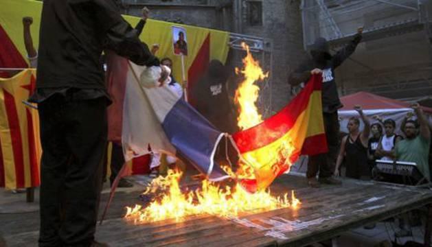 Manifestantes queman una bandera de España y otra de Francia durante la Diada.