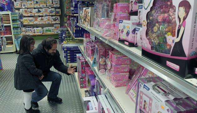 Dos personas mirando juguetes en una tienda de Pamplona.