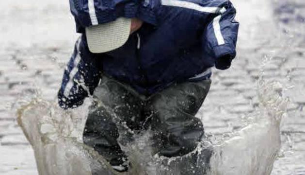 Un niño chapotea en un día lluvioso.