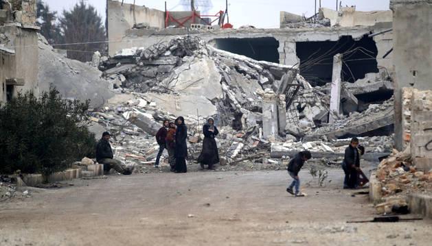 Ciudadanos sirios cerca de escombros en Alepo.