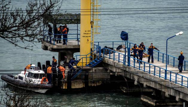 Varias personas trabajando en la recuperación de los cuerpos y los restos del avión .