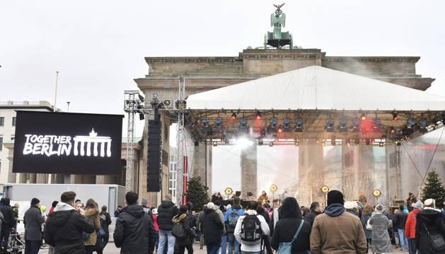 Varias personas se reúnen para disfrutar de un concierto delante de la Puerta de Brandeburgo en Berlín,
