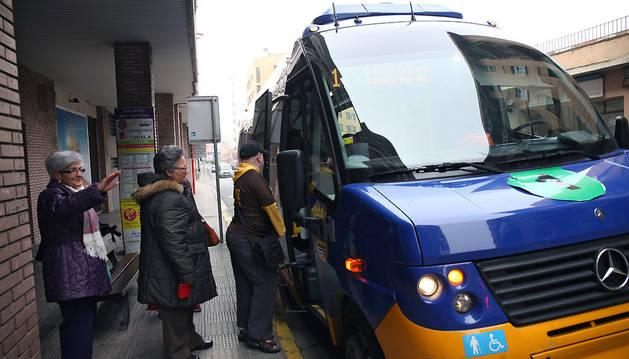 Varias personas suben a un autobús en una parada de la calle Díaz Bravo de Tudela.
