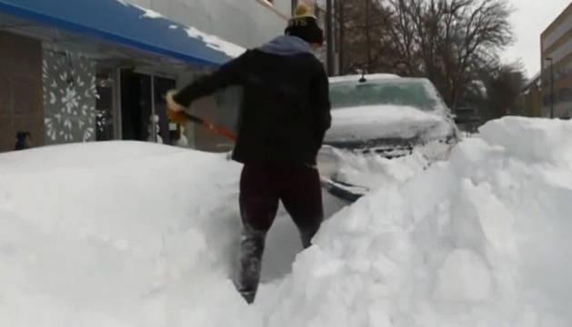 Un hombre quitando nieve de su coche y alrededores.