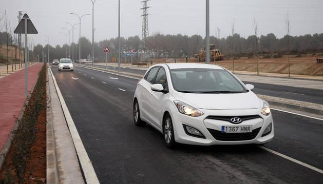 Varios vehículos circulan por el nuevo vial mientras una máquina trabaja en el talud de una de las zonas laterales.