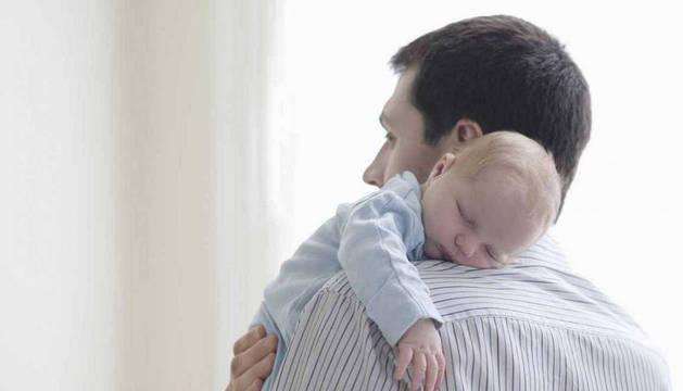 Un padre acomoda encima de su hombro a un bebé, un gesto típico después de la toma de un biberón.