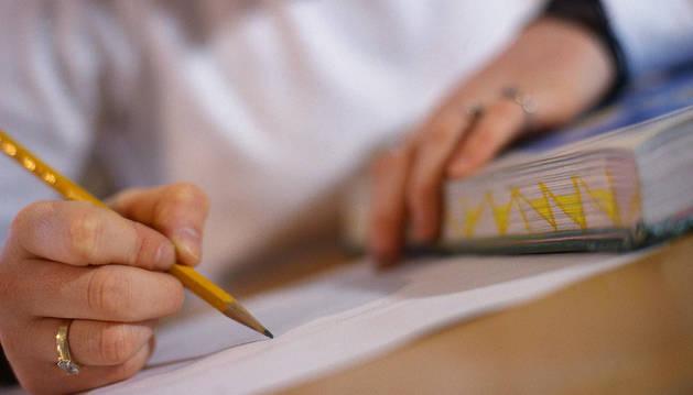 Una mujer escribe en un papel.