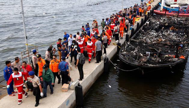 Los equipos de rescate trasladan a las personas, con el barco incendiado a la derecha.
