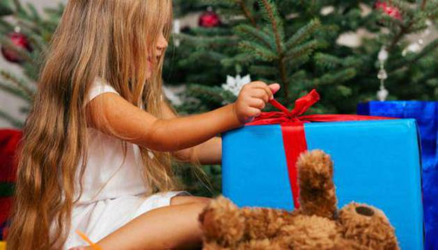 Niña desenvuelve uno de sus regalos el día de Reyes.
