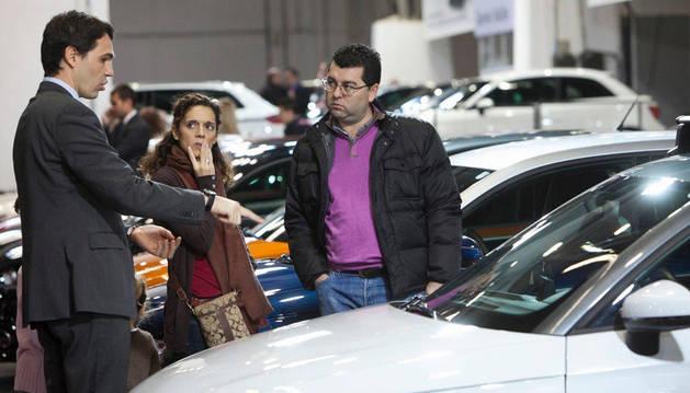 Imagen de un comercial da explicaciones a unos potenciales clientes delante del un coche en una exposición.