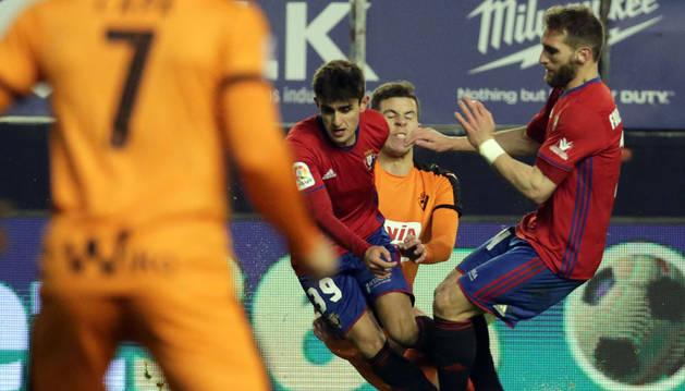 El jugador del Eibar Adrián trata de detener al canterano Aitor Lorea y a Fausto Tienza en una acción ofensiva de Osasuna.