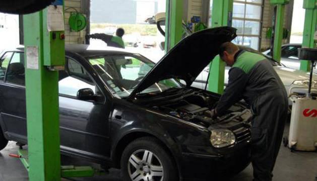 Mecánico revisa el motor de un coche.