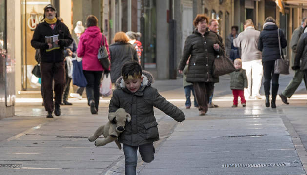 Imagen de un niño corre por la calle Mayor, muy transitada en la intersección con Baja Navarra.