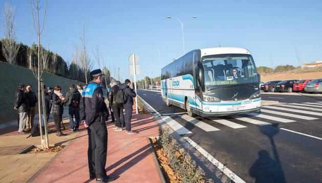 A la izquierda, autoridades asistentes a la visita al nuevo vial que une Huertas Mayores con la carretera Tarazona mientras circula un autobús por él.