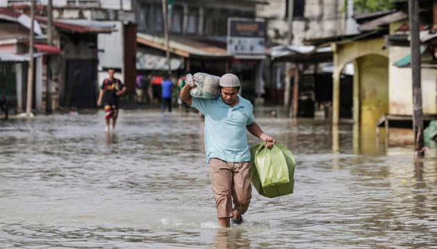 Foto de un hombre caminando por una calle inundada en el distrito de Rantau Panjang en Kelantan (Malasia)