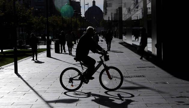 Una persona cruza en bicicleta la avenida Carlos III de Pamplona.