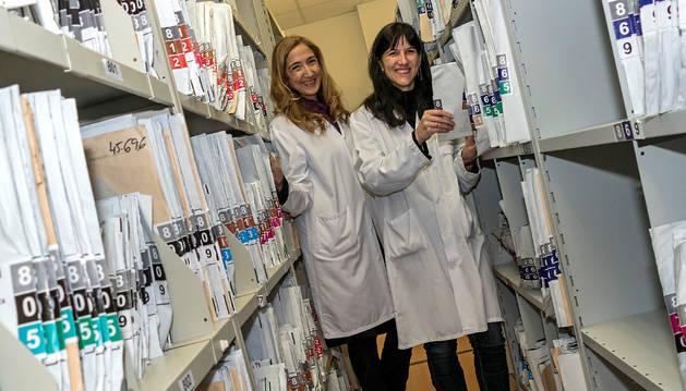 Ana Carmen Pérez Montero (izquierda) y Ainara Arabaolaza Amezua en uno de los pasillos de estanterías que guardan los sobres de historia.
